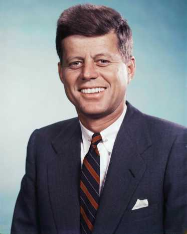 John-F-Kennedy-smiling-in-this-photo-in-a-navy-jacket-paired-with-a-stripe-tie-and-white-linen-pocket-square